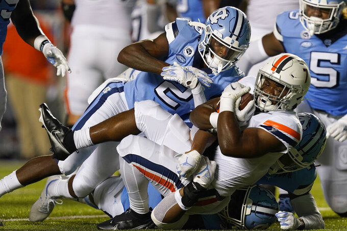 North Carolina defensive back Don Chapman (2) and teammates tackle Virginia running back Mike Hollins (7) during the first half of an NCAA college football game in Chapel Hill, N.C., Saturday, Sept. 18, 2021. (AP Photo/Gerry Broome)