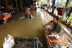 A man, right, sits on a bamboo bed as his wife, left, who wades through their flooded home following recent rains on the outskirts of Phnom Penh, Cambodia, Wednesday, Oct. 14, 2020. A Cambodian disaster official said Wednesday that more than 10,000 people have been evacuated to safety places after a tropical storm hit the country, causing the flash flood. (AP Photo/Heng Sinith)