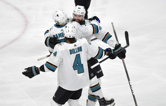 San Jose Sharks' Brent Burns, back, hugs Dylan Gambrell as teammate Brenden Dillon (4) joins the celebration after Gambrell scores a goal against the Minnesota Wild in the third period of an NHL hockey game, Saturday, Feb. 15, 2020, in St. Paul, Minn. San Jose won 2-0.(AP Photo/Tom Olmscheid)