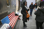 In this Sunday, Jan. 6, 2019, photo, Chinese shoppers spend their time next to a bench painted with the U.S. flag at the capital city's popular shopping mall in Beijing. A U.S. delegation led by deputy U.S. trade representative Jeffrey D. Gerrish arrived in the Chinese capital for a trade talks with China. China sounded a positive note ahead of trade talks this week with Washington, but the two sides face potentially lengthy wrangling over technology and the future of their economic relationship. (AP Photo/Andy Wong)