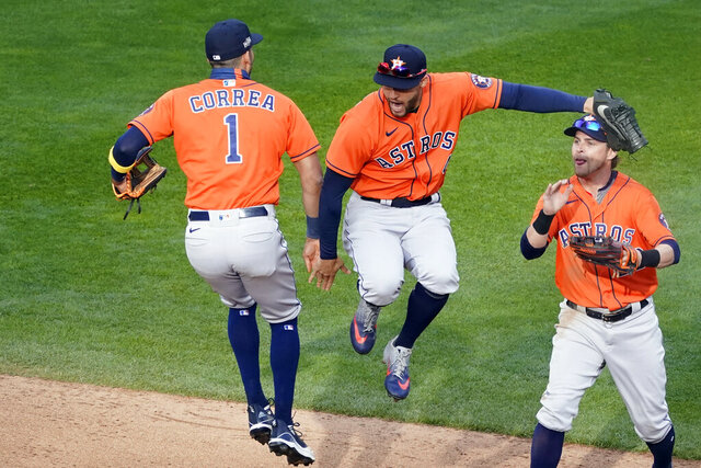 Houston Astros' Carlos Correa, left, and George Springer, center, jump in celebration of the Astros 4-1 win over the Minnesota Twins 4-1 in Game 1 of an American League wild-card baseball series, Tuesday Sept. 29, 2020, in Minneapolis. At right is Josh Reddick. (AP Photo/Jim Mone)