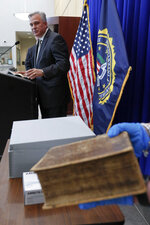 Allegheny County District Attorney Stephen Zappala talks about the efforts and ultimate recovery of the Breeches Edition Bible that FBI supervisory special agent Shawn Brokos holds during a news conference, Thursday, April 25, 2019, in Pittsburgh. The Bible that was published in 1615 was stolen from the Carnegie Library in Pittsburgh in the 1990's. It was traced to the American Pilgrim Museum in Leiden, Netherlands. (AP Photo/Keith Srakocic)