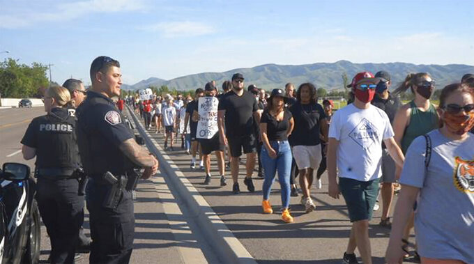 In this June 3, 2020, photo provided by Idaho State Athletics, people walk during a unity march, in Pocatello, Idaho. A strong connection between law enforcement and Idaho State student-athletes set the stage for the peaceful unity march. (Jarius Fields/Idaho State Athletics via AP)