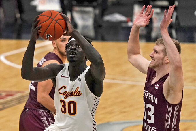 Loyola of Chicago's Aher Uguak (30) heads to the basket as Southern Illinois' Anthony D'Avanzo (33) defends during the second half of an NCAA college basketball game in the quarterfinal round of the Missouri Valley Conference men's tournament Friday, March 5, 2021, in St. Louis. (AP Photo/Jeff Roberson)