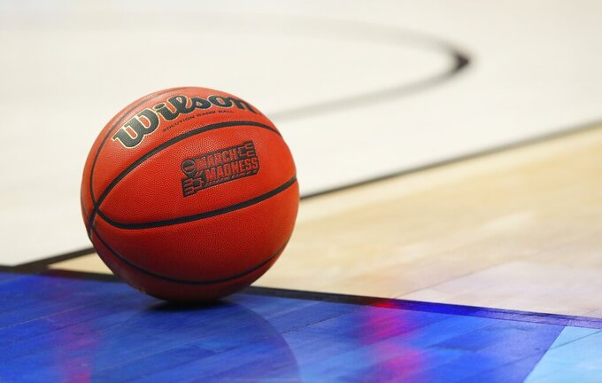 FILE -- In this March 18, 2017, file photo, an official game ball with the March Madness logo sits in the court during a second-round men's college basketball game between Villanova and Wisconsin in the NCAA Tournament in Buffalo, N.Y. Coaches did the best they could to prepare for the big moment, yet still find themselves in a scramble once it actually happened. The NCAA announced last month that the season would begin on Nov. 25 and teams are still trying to fill all the holes in their schedules.  (AP Photo/Bill Wippert, File)