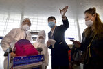 A worker directs travelers wearing face masks and suits to protect against the spread of new coronavirus at Wuhan Tianhe International Airport in Wuhan in central China's Hubei Province, Wednesday, April 8, 2020. Within hours of China lifting an 11-week lockdown on the central city of Wuhan early Wednesday, tens of thousands people had left the city by train and plane alone, according to local media reports. (AP Photo/Ng Han Guan)