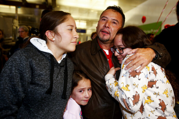 Esvin Fernando Arredondo of Guatemala reunites with his daughters Andrea, left, Keyli, right, and Alison, second from left, at Los Angeles International Airport after being separated during the Trump administration's wide-scale separation of immigrant families, Wednesday, Jan. 22, 2020, in Los Angeles. (AP Photo/Ringo H.W. Chiu)