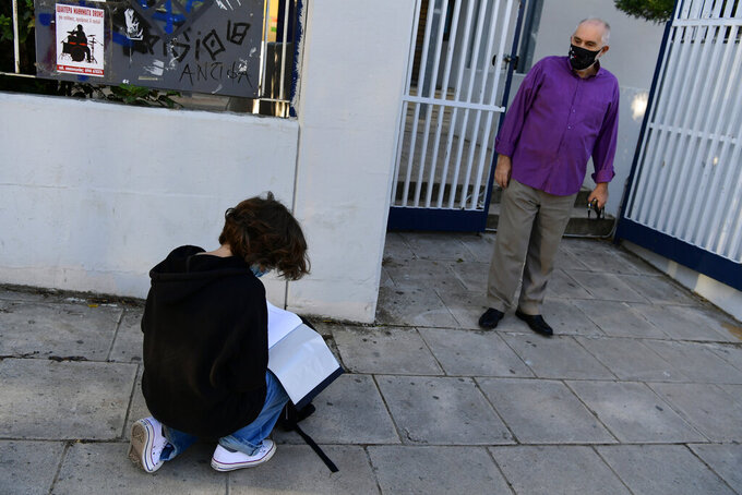 A student looks for his document stating a negative COVID-19 self-test as a teacher waits at the entrance of the school in Athens, Monday, May 10, 2021. More than 1.1 million pupils and 127,300 teachers returned to school on Monday as primary and junior high school reopened its doors with mandatory home self-tests. (AP Photo/Michael Varaklas)