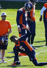 Denver Broncos quarterback Teddy Bridgewater (5) stretches in front of Drew Lock (3) during Denver Broncos OTAs at the team's headquarters Monday, May 24, 2021, in Englewood, Colo. (AP Photo/Jack Dempsey)