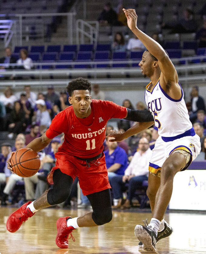 Houston's Nate Hinton, left, dribbles as East Carolina's Tyler Foster, right, defends during the second half of an NCAA college basketball game in Greenville, N.C., Wednesday, Feb. 27, 2019. (AP Photo/Ben McKeown)