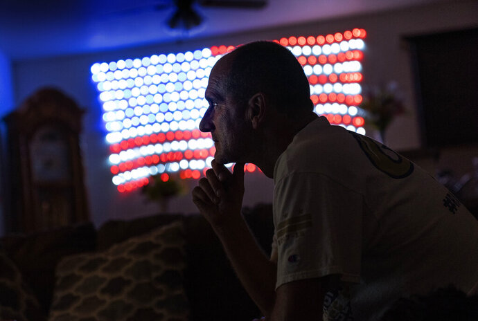Scott Rice sits in his living room watching a Fox News Channel interview with President Donald Trump in Appleton, Wis., Aug. 20, 2020. Nothing can shake Rice's faith that Trump will save the U.S. economy, not seeing businesses close or friends furloughed, not even his own hellish bout with the coronavirus. But in Appleton, a city of 75,000 people along the Fox River, the health of economy isn't judged on jobs numbers, personal bank accounts or union contracts. Instead, it's viewed through partisan lenses, filtered through the facts voters want to see and hear, and those they don't. (AP Photo/David Goldman)