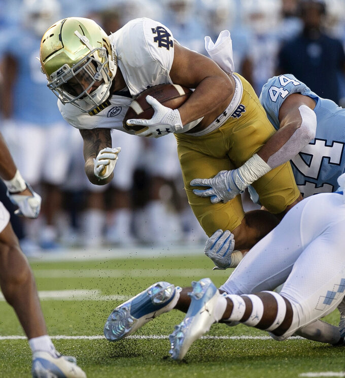 North Carolina's Jeremiah Gemmell (44) stops Notre Dame's Kyren Williams during the first quarter of an NCAA college football game Friday, Nov. 27, 2020, in Chapel Hill, N.C. (Robert Willett/The News & Observer via AP, Pool)