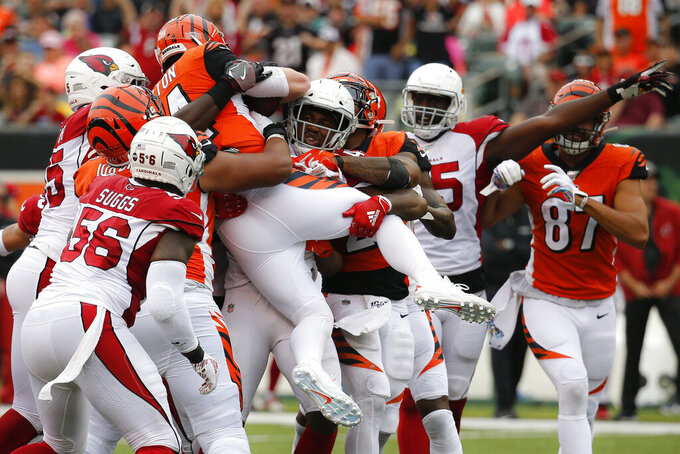Cincinnati Bengals quarterback Andy Dalton (14) is stopped mid-air on a running play in the second half of an NFL football game against the Arizona Cardinals, Sunday, Oct. 6, 2019, in Cincinnati. (AP Photo/Frank Victores)