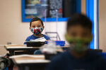 Nathan Ramos sits in a kindergarten classroom on the first day of in-person learning at Maurice Sendak Elementary School in Los Angeles, Tuesday, April 13, 2021. More than a year after the pandemic forced all of California's schools to close classroom doors, some of the state's largest school districts are slowly beginning to reopen this week for in-person instruction. (AP Photo/Jae C. Hong)