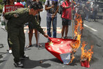 Protesters burn a mock Chinese national flag during a rally outside the Chinese Consulate at the financial district of Makati, metropolitan Manila, Philippines to mark Independence Day on Wednesday, June 12, 2019. The Philippine defense secretary says an anchored Filipino fishing boat has sunk in the disputed South China Sea after being hit by a suspected Chinese vessel which then abandoned the 22 Filipino crewmen. (AP Photo/Aaron Favila)