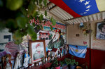 Images of Venezuela's late President Hugo Chavez are displayed amid religious iconography inside a small chapel in the 23 de Enero neighborhood, on the sixth anniversary of his death in Caracas, Venezuela, Tuesday, March 5, 2019. Chavez continues to unleash mixed feelings among Venezuelans: some remember him as the father of a revolution that claimed the majority of poor sectors, while others blame him for the deep and prolonged crisis that overwhelms the South American country. (AP Photo/Eduardo Verdugo)