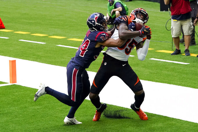 Cincinnati Bengals wide receiver Tee Higgins (85) catches a touchdown pass as Houston Texans cornerback John Reid (34) defends during the second half of an NFL football game Sunday, Dec. 27, 2020, in Houston. (AP Photo/Sam Craft)