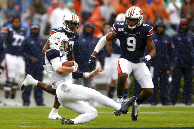 Samford quarterback Liam Welch (7) slides after carrying the ball for a first down as Auburn defensive back Jamien Sherwood (9) closes in during the first half of an NCAA college football game, Saturday, Nov. 23, 2019, in Auburn, Ala. (AP Photo/Butch Dill)