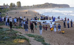 People stand near a light plane that made an emergency landing on a beach in Sydney Wednesday, May 26, 2021. The recreational plane landed safely on a Sydney beach with three people aboard including a baby on Wednesday after its single engine failed, officials said. (AP Photo/Mark Baker)