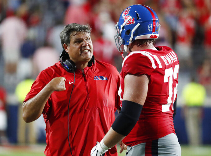 Mississippi coach Matt Luke confers with offensive lineman Royce Newman (72) during the second half of an NCAA college football game against Arkansas, Saturday, Sept. 7, 2019, in Oxford, Miss. Mississippi won 31-17. (AP Photo/Rogelio V. Solis)