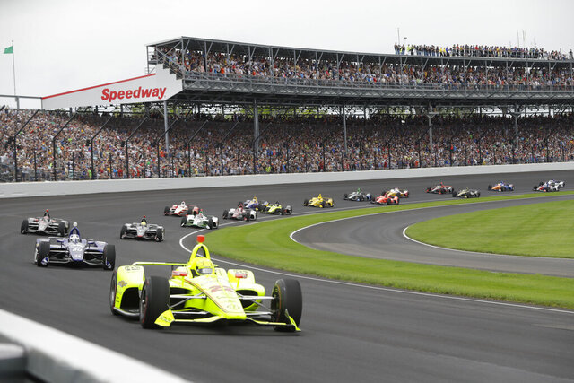 FILE - In this May 26, 2019, file photo, Simon Pagenaud, of France, leads the field through the first turn on the start of the Indianapolis 500 IndyCar auto race at Indianapolis Motor Speedway, in Indianapolis. The Indianapolis 500 scheduled for May 24 has been postponed until August because of the coronavirus pandemic and won't run on Memorial Day weekend for the first time since 1946.  The race will instead be held Aug. 23. (AP Photo/Darron Cummings, File)
