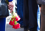 In this grab taken from a footage provided by the Russian State Atomic Energy Corporation ROSATOM press service, a woman holds roses as she and other people gather for the funerals of five Russian nuclear engineers killed by a rocket explosion in Sarov, the closed city, located 370 kilometers (230 miles) east of Moscow, which has served as a base for Russia's nuclear weapons program since the late 1940s, Russia, Monday, Aug. 12, 2019. Russia's Rosatom state nuclear concern said Thursday's explosion at a military testing range in northwestern Russia occurred while the engineers were testing a