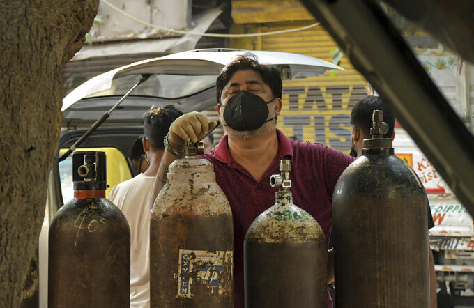 Family member of a COVID-19 patient reacts as he waits to refill an oxygen cylinder at a gas supplier facility in New Delhi, India, Saturday, May 8, 2021. Infections have swelled in India since February in a disastrous turn blamed on more contagious variants as well as government decisions to allow massive crowds to gather for religious festivals and political rallies. (AP Photo/Ishant Chauhan)