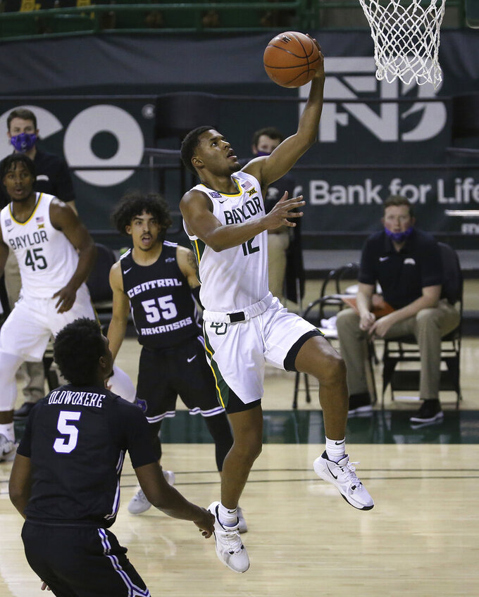 Baylor guard Jared Butler (12) drives between Central Arkansas guard DeAndre Jones (55) and Central Arkansas guard Masai Olowokere (5) in the first half of an NCAA college basketball game, Tuesday, Dec. 29, 2020, in Waco, Texas. (AP Photo/ Jerry Larson)