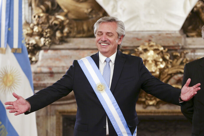 Argentina's President Alberto Fernandez opens his arms at the presidential palace in Buenos Aires, Argentina, Tuesday, Dec. 10, 2019. Fernandez became president of Argentina on Tuesday, returning the country's Peronist political movement to power amid an economic crisis and rising poverty. (AP Photo/Daniel Jayo)