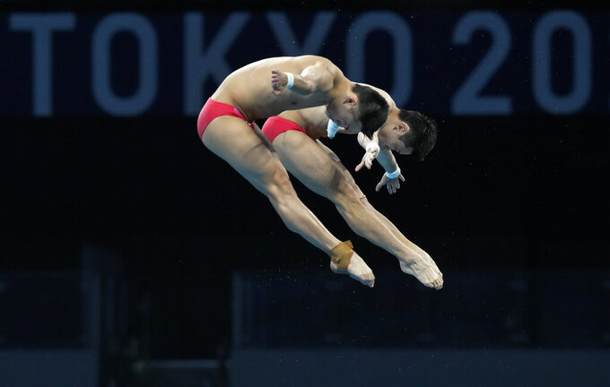 Yuan Cao and Aisen Chen of China compete during the men's synchronized 10m platform diving final at the Tokyo Aquatics Centre at the 2020 Summer Olympics, Monday, July 26, 2021, in Tokyo, Japan. (AP Photo/Dmitri Lovetsky)