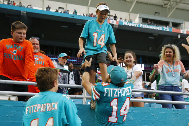FILE - In this Dec. 1, 2019, file photo, Miami Dolphins quarterback Ryan Fitzpatrick (14) grabs his kids at the end of the second half at an NFL football game again st the Philadelphia Eagles in Miami Gardens, Fla. Ryan Fitzpatrick is spending his coronavirus lockdown in Arizona with his wife and seven children, and hoping to get a chance soon to begin mentoring first-round draft pick Tua Tagovailoa.(AP Photo/Brynn Anderson, File)