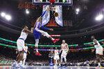 Philadelphia 76ers' Matisse Thybulle, center, dunks the ball with New York Knicks' Dennis Smith Jr., left, defending during the first half of an NBA basketball game, Wednesday, Nov. 20, 2019, in Philadelphia. (AP Photo/Chris Szagola)