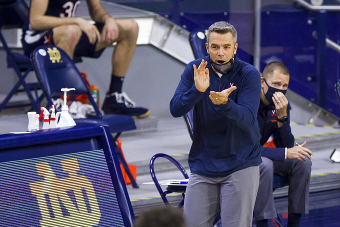 Virginia coach Tony Bennett claps for the team during the second half of an NCAA college basketball game against Notre Dame on Wednesday, Dec. 30, 2020, in South Bend, Ind. Virginia won 66-57. (AP Photo/Robert Franklin)
