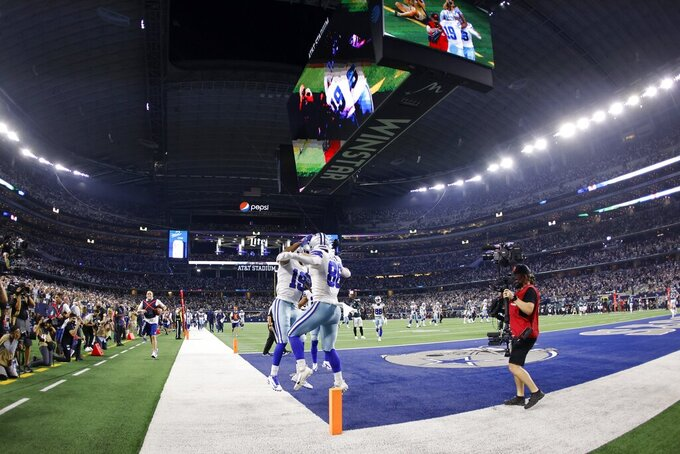 Dallas Cowboys' Amari Cooper (19) and Dalton Schultz (86) celebrate a touchdown catch made by Schultz in the first half of an NFL football game against the Philadelphia Eagles in Arlington, Texas, Monday, Sept. 27, 2021. (AP Photo/Ron Jenkins)