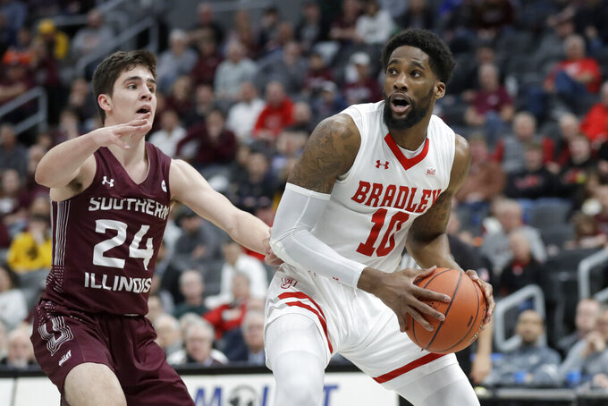 Bradley's Elijah Childs (10) heads to the basket as Southern Illinois' Trent Brown (24) defends during the first half of an NCAA college basketball game in the quarterfinal round of the Missouri Valley Conference men's tournament Friday, March 6, 2020, in St. Louis. (AP Photo/Jeff Roberson)