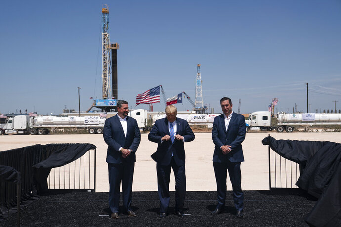 President Donald Trump adjusts his jacket as he stands with Double Eagle Energy co-CEOs Cody Campbell, left, and John Sellers, right before viewing the Double Eagle Energy Oil Rig, Wednesday, July 29, 2020, in Midland, Texas. (AP Photo/Evan Vucci)