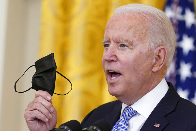 President Joe Biden holds up a mask as he announces from the East Room of the White House in Washington, Thursday, July 29, 2021, that millions of federal workers must show proof they've received a coronavirus vaccine or submit to regular testing and stringent social distancing, masking and travel restrictions in an order to combat the spread of the coronavirus. (AP Photo/Susan Walsh)