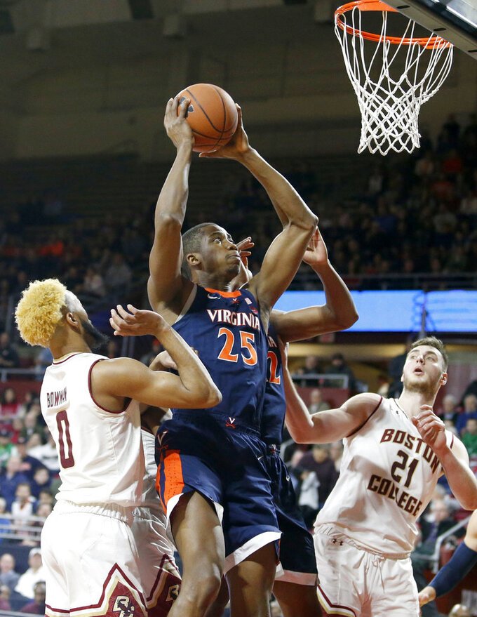Virginia forward Mamadi Diakite (25) drives to the basket against Boston College guard Ky Bowman (0) and forward Nik Popovic (21) during the first half of an NCAA basketball game Wednesday, Jan. 9, 2019, in Boston. (AP Photo/Mary Schwalm)