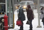 Commuters board a bus at the corner of 6th St. and 2nd Ave. as a powdery dusting of snow falls ahead of a large expected snowstorm Friday, Jan. 17, 2020, in downtown Minneapolis, Minn. (David Joles/Star Tribune via AP)