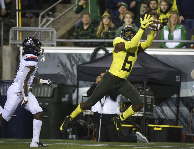 Oregon's Juwan Johnson, right, pulls down a Justin Herbert pass on his way to a touchdown ahead of Arizona's Christian Roland-Wallace, left, during the second quarter of an NCAA college football game Saturday, Nov. 16, 2019, in Eugene, Ore. (AP Photo/Chris Pietsch)