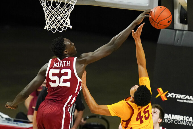 """FILE - Oklahoma forward Kur Kuath (52) blocks a shot by Iowa State guard Rasir Bolton during the second half of an NCAA college basketball game in Ames., in this Saturday, Feb. 20, 2021, file photo. Marquette has added former Oklahoma forward Kur Kuath to its roster. """"He's a player who we got to know as an opponent while he was at Oklahoma, and he's one of the best two-way bigs we played against,"""" Marquette coach Shaka Smart said in a university release. (AP Photo/Charlie Neibergall, File)"""