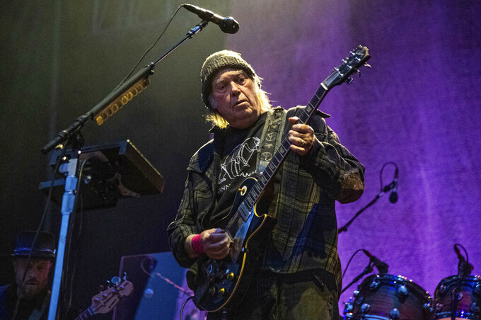 """FILE - In this May 25, 2019, file photo, Neil Young performs at the BottleRock Napa Valley Music Festival at Napa Valley Expo in Napa, Calif. Young has become the latest artist to strike gold with his song catalog. The Hipgnosis Songs Fund, a British investment company, announced that it had acquired a 50 percent stake in Young's catalog of some 1,180 songs that include """"Heart of Gold,"""" """"Rockin' in the Free World"""" and """"Cinnamon Girl."""" (Photo by Amy Harris/Invision/AP, File)"""