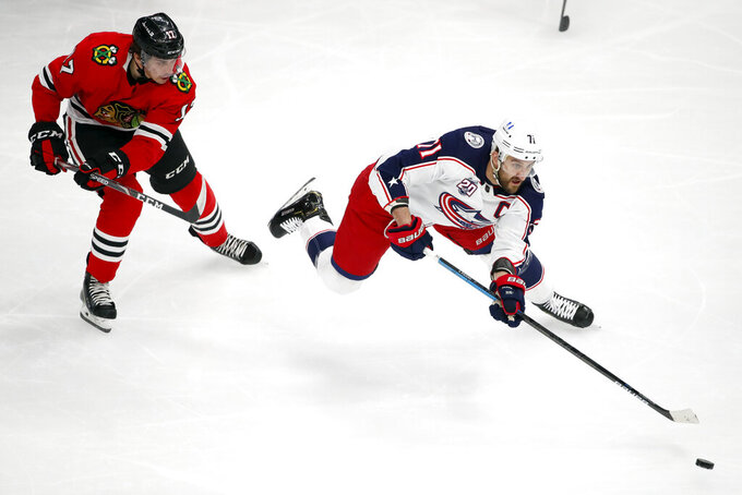 Columbus Blue Jackets left wing Nick Foligno (71) is tripped by Chicago Blackhawks center Dylan Strome (17) during the first period of an NHL hockey game Sunday, Jan. 31, 2021, in Chicago. (AP Photo/Jeff Haynes)