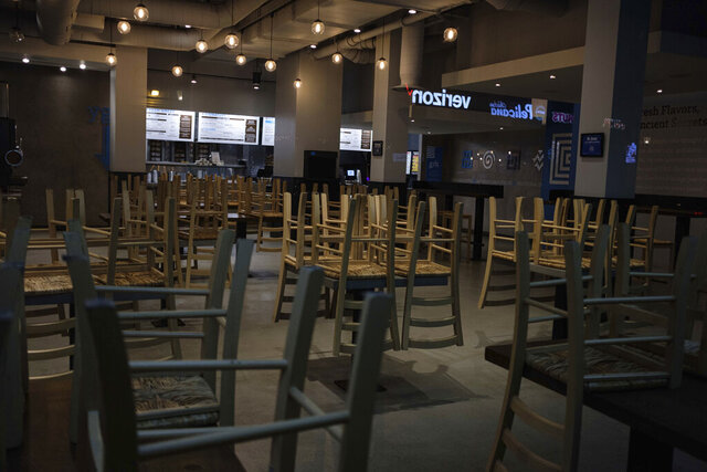 FILE - In this March 16, 2020 file photo, chairs hang stacked on empty tables at a closed restaurant in New York.  Small business owners across the country waited again Wednesday, April 8,  to receive loan money under the government's $2 trillion coronavirus relief program. Despite a few reports that some companies had received their loans, the vast majority of the hundreds of thousands of owners who began applying for the loans on Friday were still in limbo. (AP Photo/Yuki Iwamura, File)