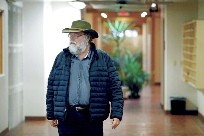 In this Nov. 6, 2019 photo, Santa Fe New Mexican reporter Steve Terrell walks out of the newsroom after a long day, in Santa Fe, N.M. Terrell, 66, is retiring from The New Mexican on Friday, Nov. 22 after 33 years at the newspaper and nearly 40 years as a reporter in Santa Fe. (Luis Sanchez Saturno/Santa Fe New Mexican via AP)