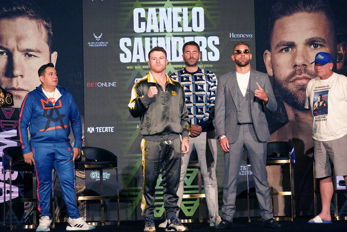 Boxers Canelo Alvarez of Mexico, center left, and Billy Joe Saunders of Great Britain, center right, pose for cameras as promoter Eddie Hearn, center, trainer Eddy Reynoso, left, and Saunders' father Tommy Saunders, right, all look on during a pre-fight news conference, Thursday, May 6, 2021, in Arlington, Texas. Alvarez and Saunders fight on Saturday, May 8, 2021, for the unified super middleweight world championship. (AP Photo/LM Otero)