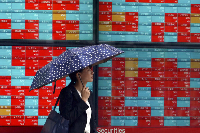 A woman walks past an electronic stock board showing Japan's Nikkei 225 index at a securities firm in Tokyo Friday, July 12, 2019. Shares in Asia are mostly higher after a turbulent day on Wall Street ended with the Dow Jones Industrial Average closing above 27,000 for the first time. (AP Photo/Eugene Hoshiko)