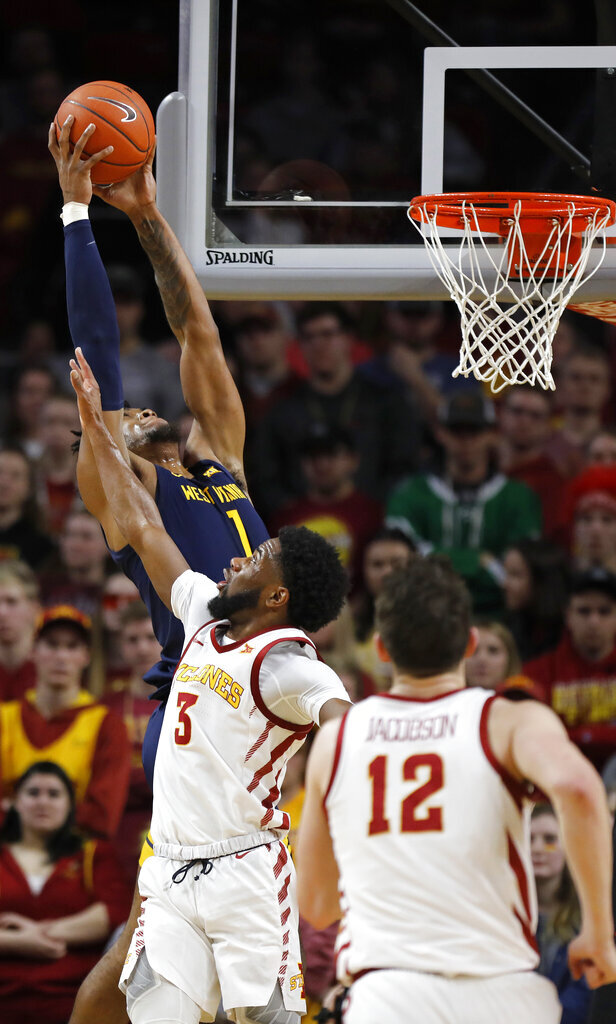 West Virginia forward Derek Culver, top, jumps aboe Iowa State guard Tre Jackson, center, for a rebound during the first half of an NCAA college basketball game Tuesday, March 3, 2020, in Ames, Iowa. (AP Photo/Matthew Putney)