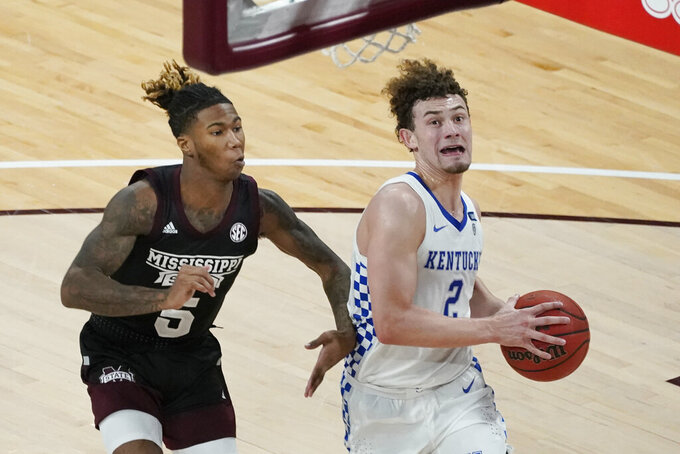 Kentucky guard Devin Askew (2) runs past Mississippi State guard Deivon Smith (5) to attempt a layup during the second half of an NCAA college basketball game in Starkville, Miss., Saturday, Jan. 2, 2021. (AP Photo/Rogelio V. Solis)