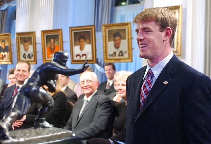 FILE - USC quarterback Carson Palmer, right, smiles at the Heisman Trophy after being named the 2002 Heisman Trophy winner at The Yale Club in New York, in this Dec. 14, 2002, file photo. Heisman Trophy winner Carson Palmer and former Oklahoma coach Bob Stoops are among the 13 former players and coaches who make up the latest College Football Hall of Fame class.  The National Football Foundation announced the newly elected hall of famers Monday, Jan. 11, 2021. This class will be inducted in December. (AP Photo/Suzanne Plunkett, File)